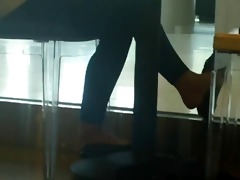 candid shoeplay dangling feet in coffee shop